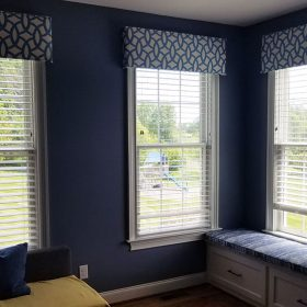 three windows with blue valances